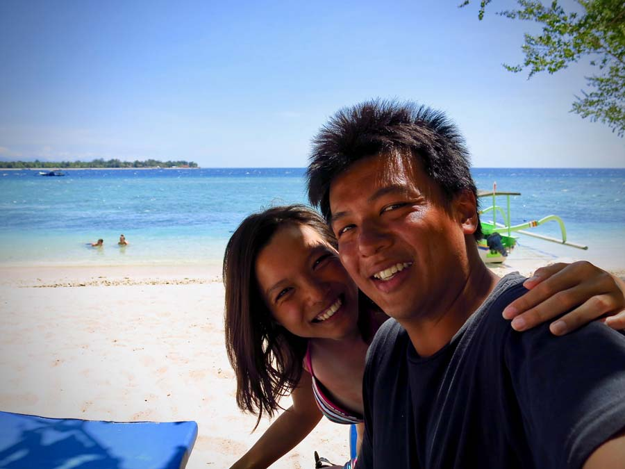Couple enjoying and relaxing at the beach of Gili Meno